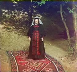 Donna georgiana in piedi su un kilim fine del XIX secolo.